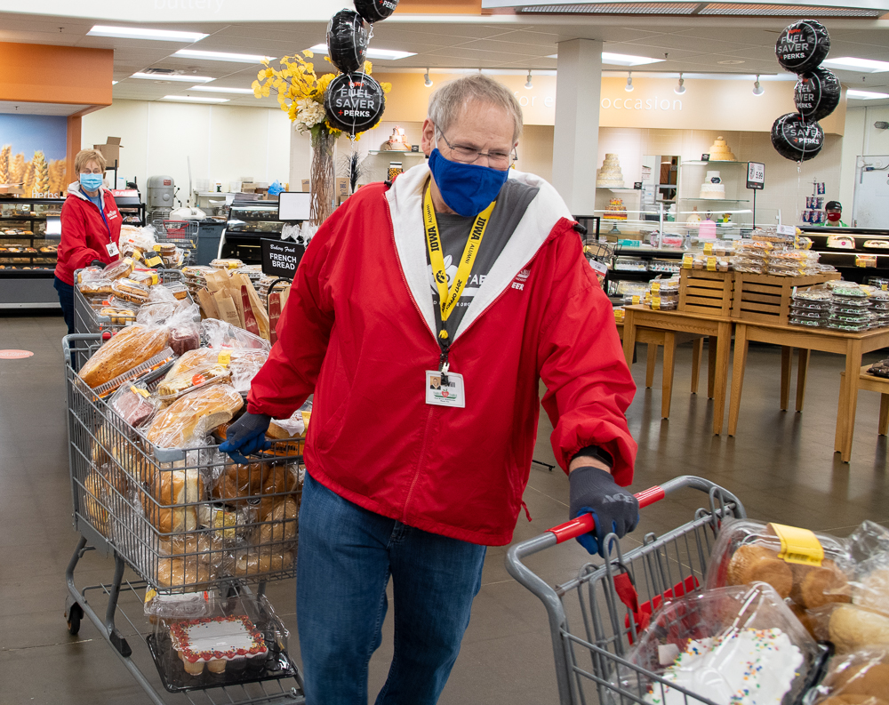 Volunteers push carts of donated bread through a grocery store partner.