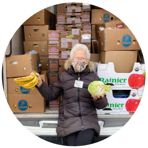 Mary holds bananas and cabbage while sitting in a food rescue van on her route
